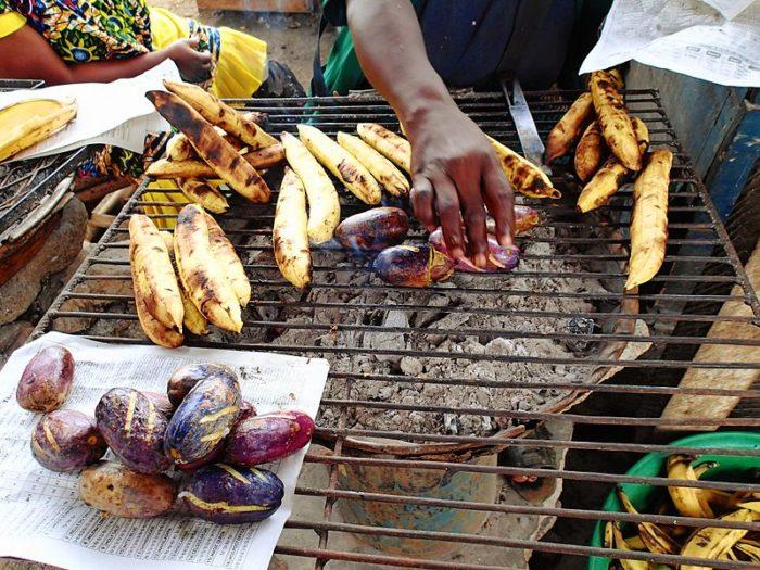 Image 4: Sur le barbecue cuisent des safous et des bananes plantain. Les consommateurs s'arrêtent, marchandent et repartent avec leur lot emballé dans le journal du matin.